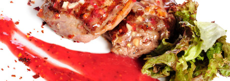Grilled pork steaks with raspberry sauce and leaf of lettuce